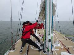 2 people at the mast working together to get the halyard up.