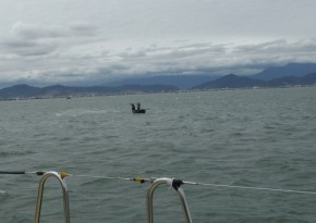 Fisherman casting net from their small boat with waves building