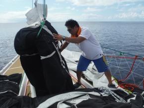 Han directing putting Yankee sail into sail locker.